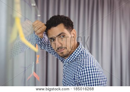 Thoughtful executive leaning on whiteboard in office