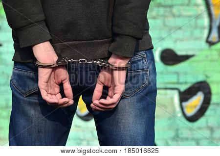 Close-up Of Male Hands, Handcuffed Against A Graffiti Background On A Brick Wall