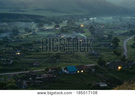 Rural settlement in the mountains at dusk. Wooden houses huts heated by stoves. Smoke from the pipes. The hills. Altai.