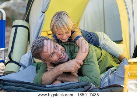 Playful little boy lying on father in tent at campsite