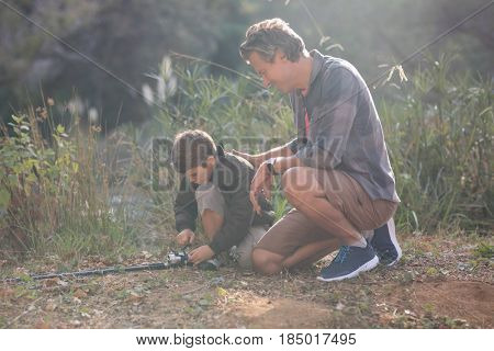 Father and son with fishing rod kneeling on field during sunny day