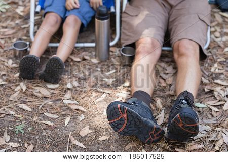 Low section of father and son sitting on chairs in forest