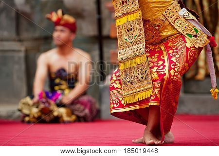 Asian travel background. Beautiful Balinese dancer woman in traditional Sarong costume dancing Legong dance. Legs movements. Arts culture of Indonesian people Bali island festivals.