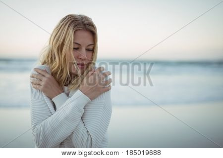 Young woman with eyes closed hugging self at beach during dusk