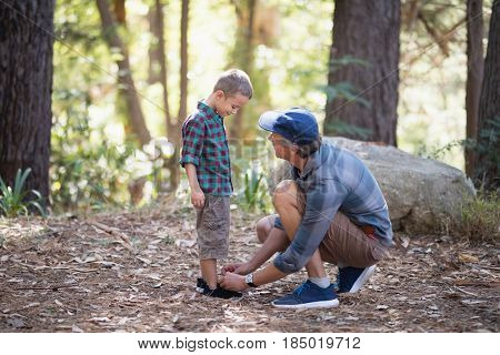 Father tying shoelace of son while hiking in forest