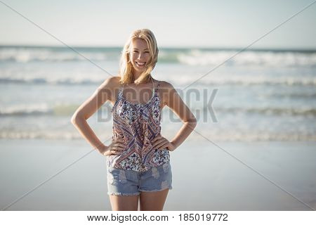 Portrait of smiling woman standing with hands on hip at beach during sunny day