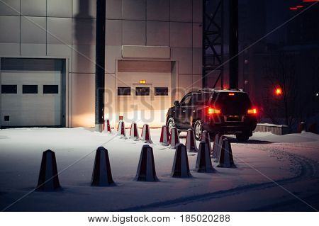 The black car calls into the automatic gate on a winter evening. Offroad car.