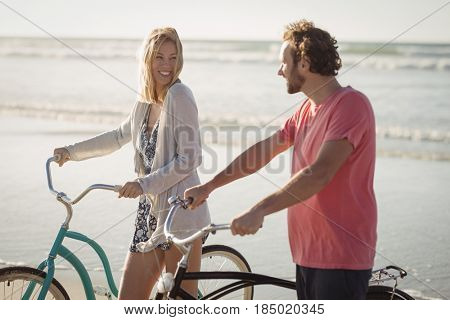 Happy young couple with bicycles at beach during sunny day