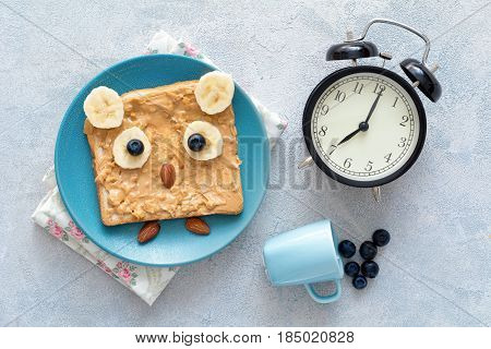 Funny owl toast with peanut butter, banana, blueberries and almonds on a blue plate, a clock and tiny cup of blueberries. Top view of healthy cute and healthy breakfast for kids. Good morning concept