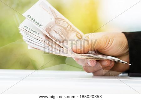 business hands holding money with Thai baht notes with abstract background