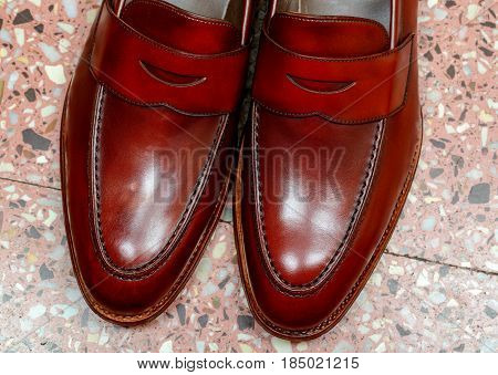 Pair of leather burgundy penny loafer shoes together on floor background one by one. Horizontal close-up image