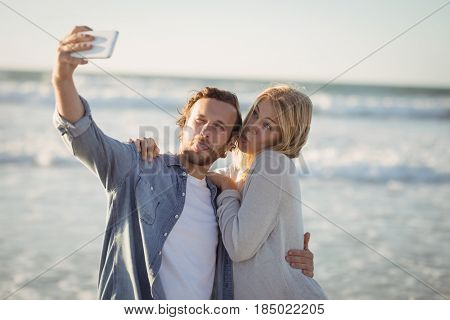 Young couple taking selfie at beach during sunny day