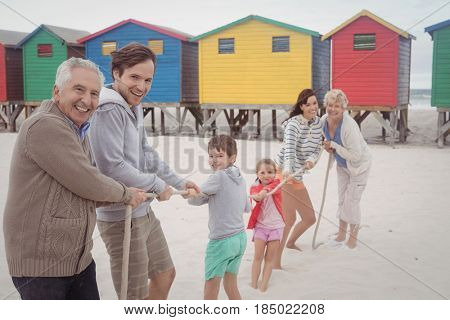 Portrait of happy multi-generation family playing tug of war at beach