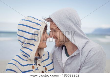 Smiling couple wearing hooded sweater at beach during winter