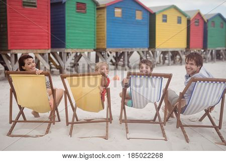 Portrait of family resting on lounge chairs at beach