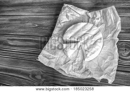 Camembert cheese on white paper and rustic dark wooden background. Top view. Black and white