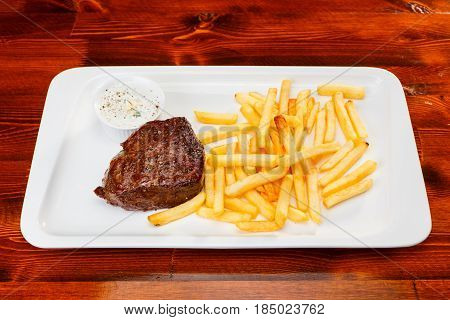 Rustic grilled beefsteak with french fries and garlic sauce