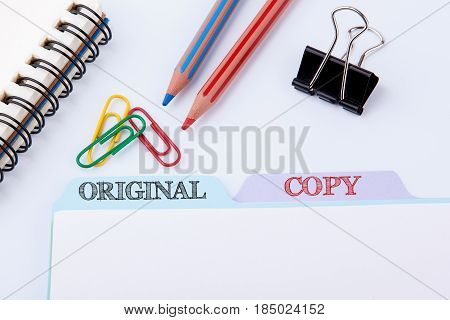 Original and Copy. Folder Register on a white Office Table.