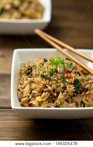 Fried rice. Basil chicken fried rice with chopsticks on a wooden background viewed from above. This thai inspired meal is perfect for a quick lunch or served as side dish.