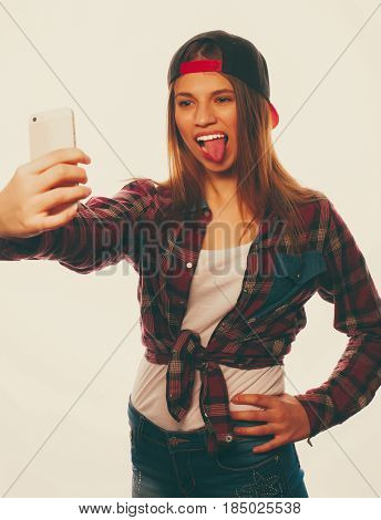 People, lifestyle and tehnology concept: pretty teen girl wearing hat, taking selfies with her smart phone - isolated on white