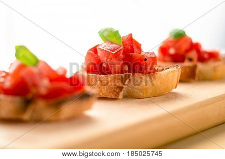 Tomato basil bruschetta. Bruschetta is an italian food made of chopped tomatoes garlic basil and fresh herbs on a toasted bread. These are traditionally served as snacks or antipasti (appetizers).