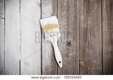 White paint space with paintbrush on wood background