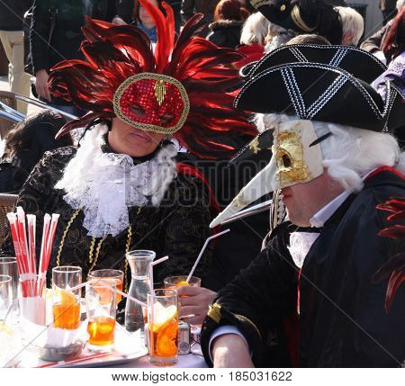 People In Costumes And Masks Having Drinks At The Venice Carnival