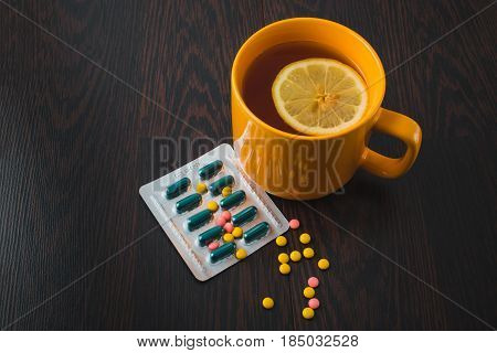 Healthcare, Traditional Medicine And Flu Concept - Tea Cup With Lemon And Pills. Medical Pills And H