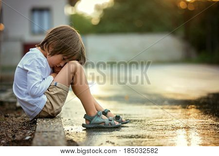 Sad Little Boy, Sitting On The Street In The Rain, Hugging His Teddy Bear