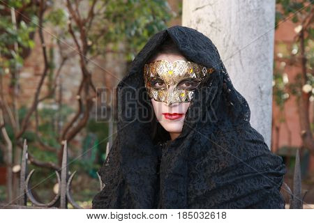 Woman In A Black Costume And Golden Mask Posing At The Venice Carnival In Venice, Italy