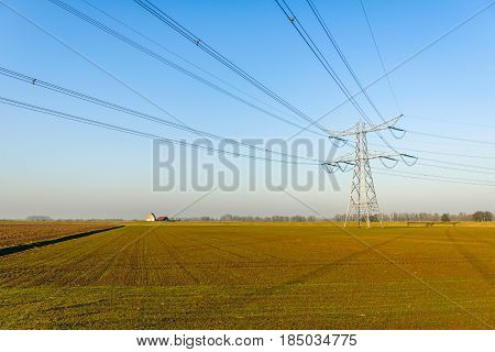 High voltage pylon and cables against a blue sky in a flat agricultural landscape in the Netherlands. It is a sunny day in the end of the winter season
