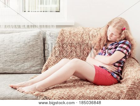 the child with stomach ache in sofa
