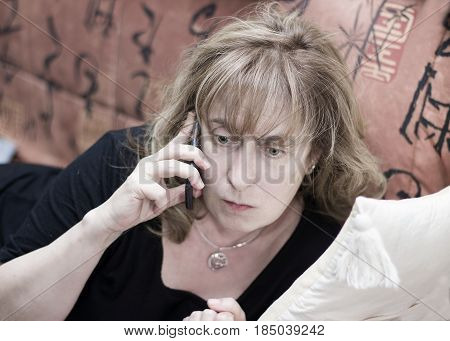 Woman seems upset while talking on mobile phone laying on the sofa Cropped filtered portrait with shallow depth of field