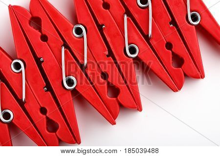Red Plastic Clothespins On A White Background.