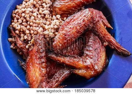 Close up tasty cooked chicken wings and boiled buckwheat on blue plate