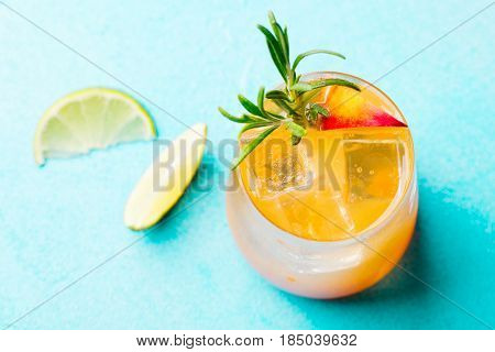 Peach cocktail fizz ice tea with fresh rosemary and lime Blue background. Copy space. Top view.
