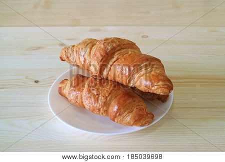 Fresh whole wheat Croissant pastries served on natural light color wooden table