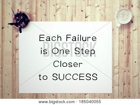 Inspiring motivation quote handwritten on a notepad each failure is one step closer to success. White pad paper image.