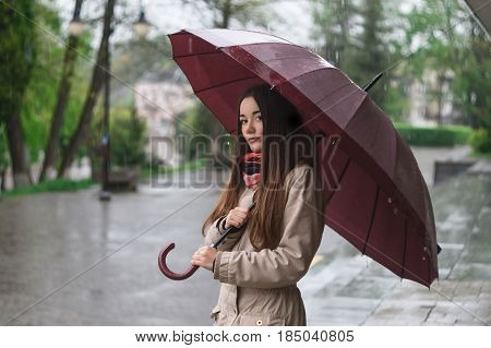 A girl in a jacket with an umbrella walks in rainy day. Rain.