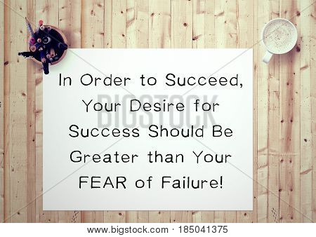Inspiring motivation quote handwritten on a notepad in order to succeed, your desire for success should be greater than your fear of failure. White pad paper image.