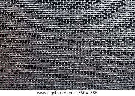 Close up black metal perforated surface of loudspeakers