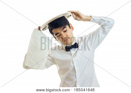 a young waiter in a white shirt and black bow tie raised ware tray on his head and closed his eyes isolated on white background