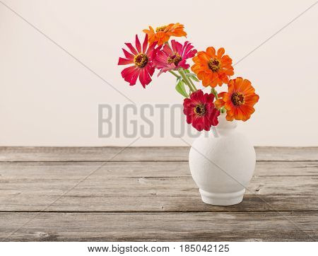 Bouquet of zinnia flowers on wooden table