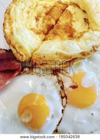 Low carb breakfast with omelette, fried eggs and bacon