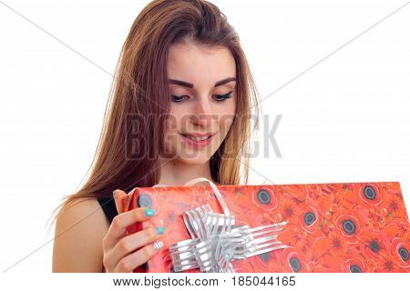 young beautiful girl holding a red Giftwrap and smiling isolated on white background