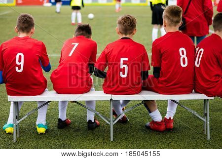 Youth Sport Soccer Team Sitting on Bench. Young Footballers as Substitute Players Watching Football Tournament Match. Boys Kicking Football Soccer Game in the Background