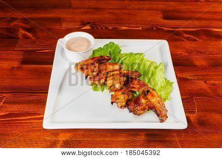 chicken wings with salad leaves and sauce on wooden background