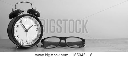 Alarm clock and glasses on wooden table. Black and white image.