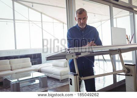 Portrait of mature interior designer standing by workbench in office