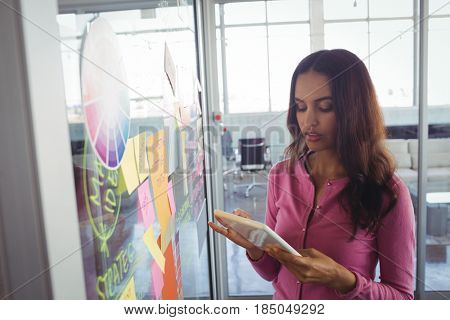 Focused female designer holding digital tablet by adhesive notes on glass in office